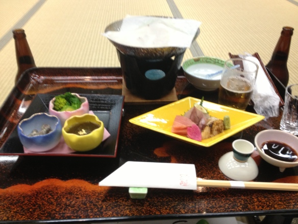 My table laid out with sashimi, nabe and a shot of sake.