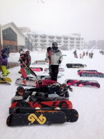 Snowboards and snowboarders outside the restaurant
