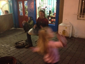 A girl dancing around a busker playing the 'hang' in Ireland.